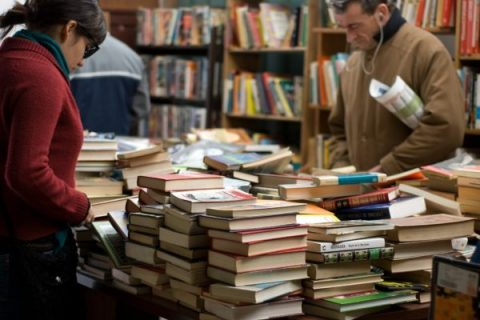 People browsing a table with stacks of piled books.